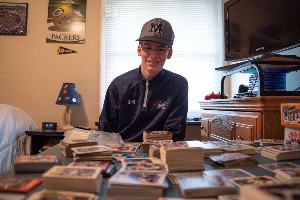 Gabriel Carter looks at his baseball card collection in his bedroom.