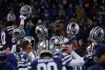 K-State's sideline celebrates by holding their helmets
