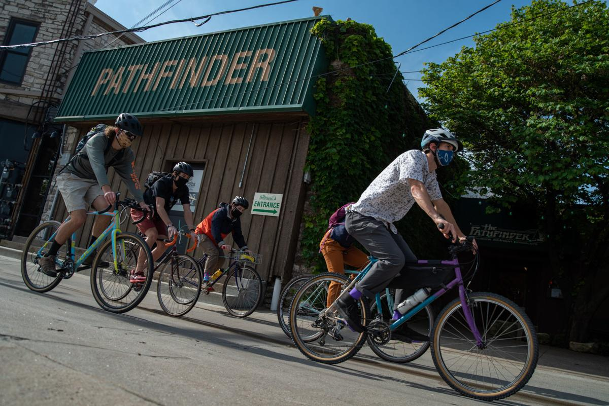 From left, Daniel Haake, Kevin White, Kyler Reith, Courtney Markle and Ben Sachs ride their bikes down the alleyway behind Pathfinder on their way to work on Wednesday morning.