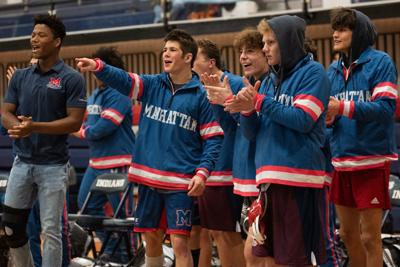 The Manhattan wrestling team's bench reacts as their teammate Talique Houston wrestles Bryce Yeagley.