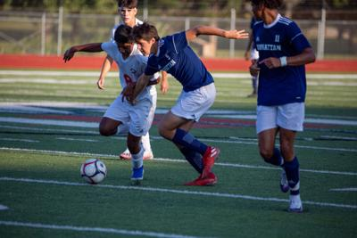 Carlos Batres, a junior midfielder, races Michael Ohler, a senior forward. The Manhattan High School Indians beat the Great Bend High School Panthers 6 to 1 on Tuesday.