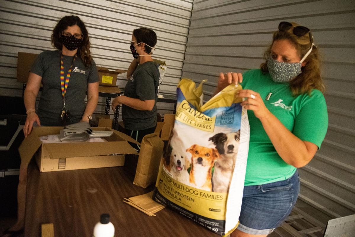 From left, Sarah Velasquez, Amanda Campanella and Erin Bishop get ready to fill up bags with dog food at their facility on Thursday. All three women are on the Pet Food Pantry Committee and are Riley County Humane Society Board Members.