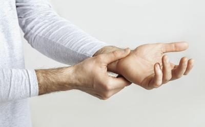Carpal tunnel syndrome and wrist pain. Man holds to sore spot
