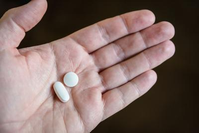 two white pills in the palm