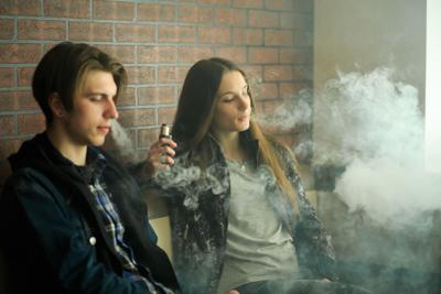 Vape teenagers. Young cute girl in sunglasses and young handsome guy smoke an electronic cigarettes in the vape bar. Bad habit that is harmful to health.