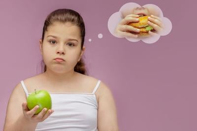 the girl eats a green Apple, but dreams about hamburger.