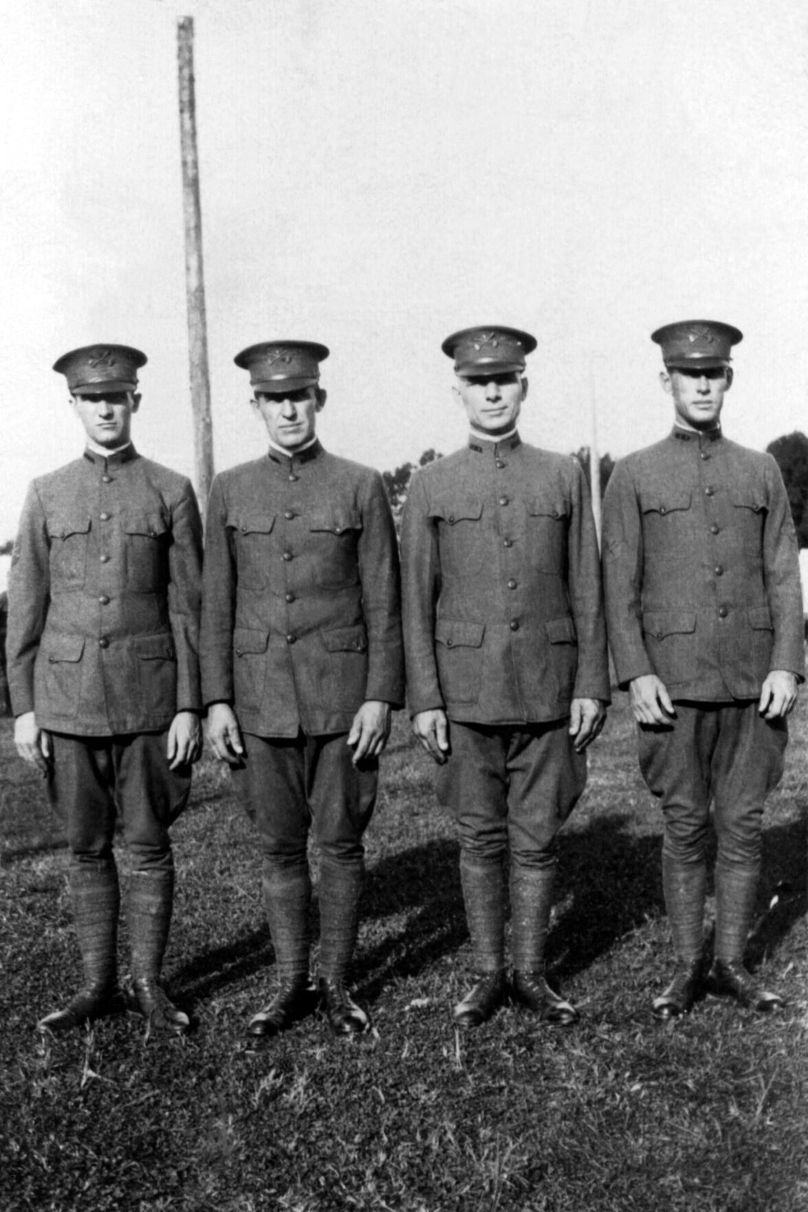 Portrait of four military men in uniform standing outdoors in a line; circa WW1.