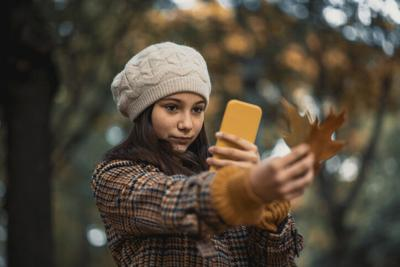Teenage girl taking picture of autumn leaf's in the park