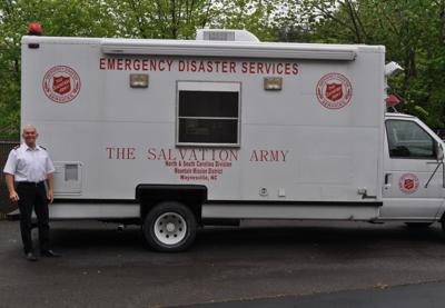 Major David Cope stands beside Salvation Army canteen