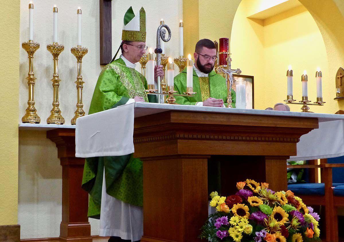 Fr. Paul McNulty making profession of faith as Bishop Jugis listens