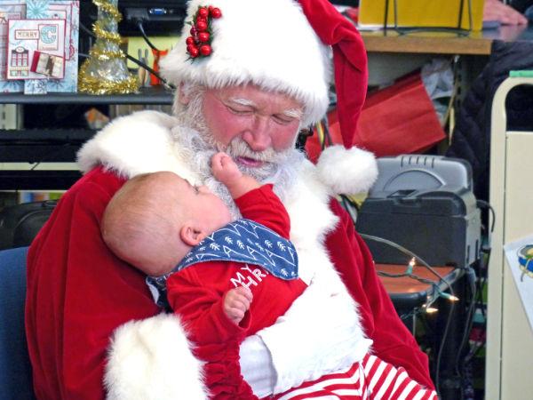 Ryker Nelke plays with Santa Claus' beard