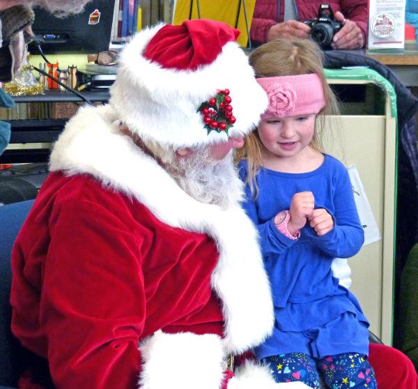 Santa Claus leans in to listen to Adi DeShazo