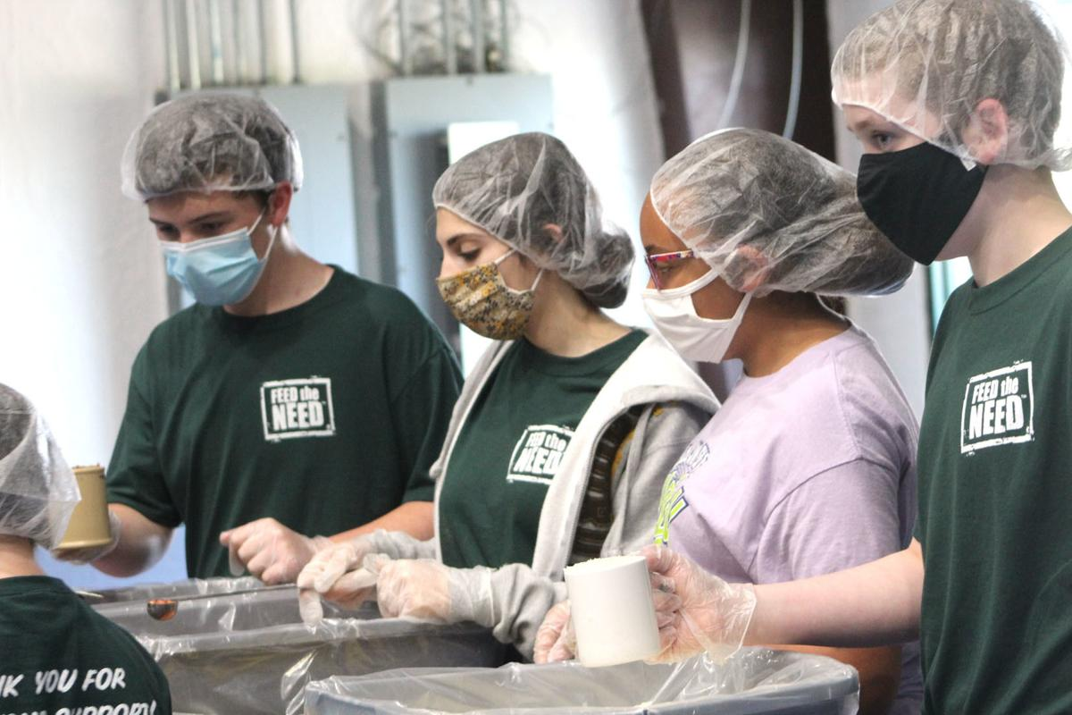 Local students pack food boxes for Haitian orphans