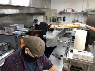 Staff members work in the kitchen of Grinders and Gravy.