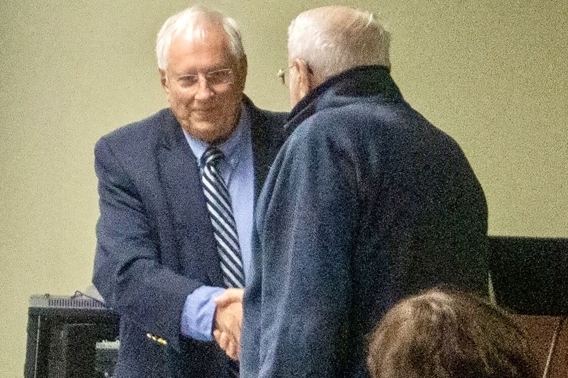 Leo Santowasso, chairman of the Moore County Board of Health, shakes hands with Robert Wittmann, outgoing health director, on Oct. 11, 2021.