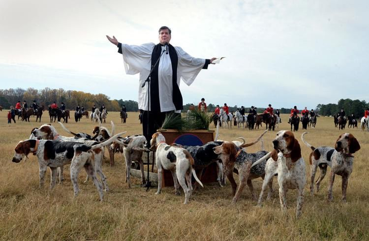 A priest officiates the Blessing of the Hounds at Buchan Field