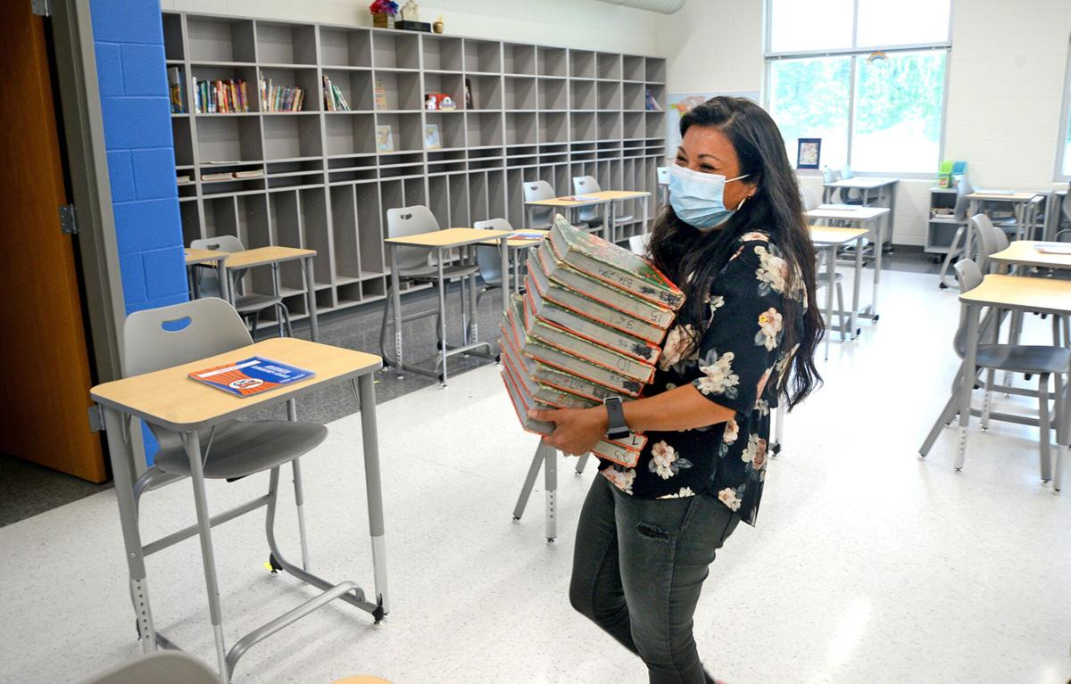 Candace Necochea carries a stack of textbooks