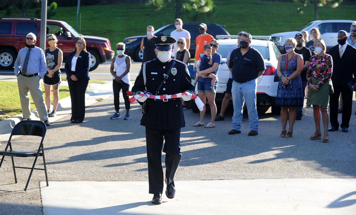 A flag bearing the name of first responders killed in 9/11 is presented for display at the Southern Pines Police Department