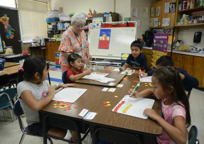 Substitute teacher Vera Warren works with first graders at Robbins Elementary School.