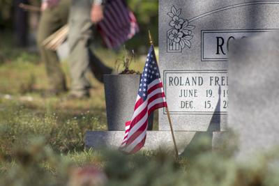 A volunteer places flags near the headstone of a veteran in Woodlawn Cemetery