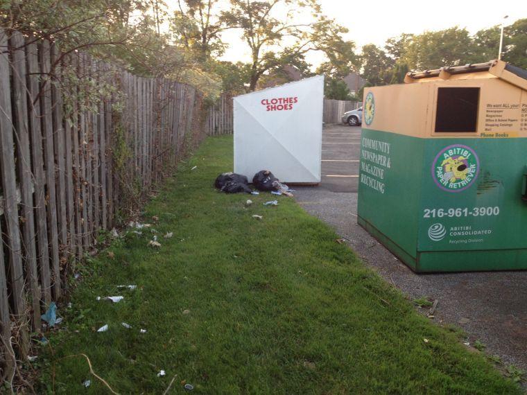 Trash outside a clothing bin