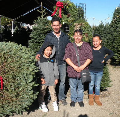 The Suarez family enjoying their freshly picked Christmas tree at Troop 152's lot