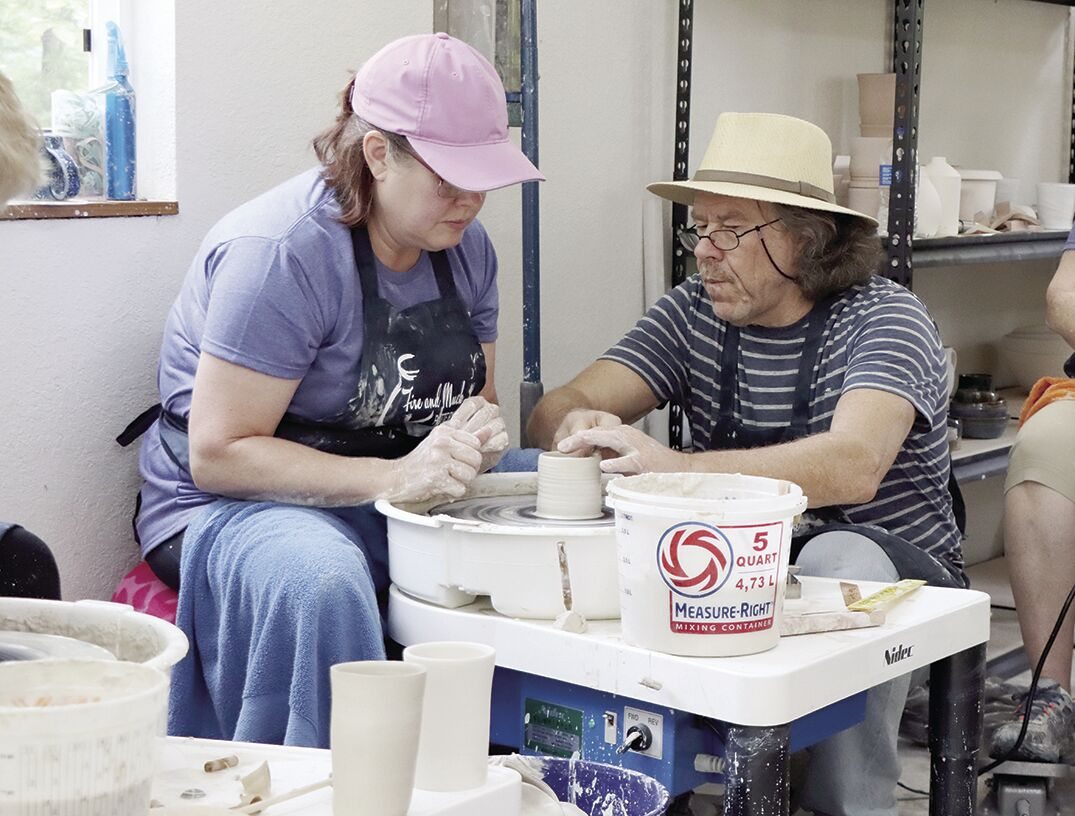 Simon Leach assists Shaunalynn Santee with her cylinder in the first day of his local workshop.