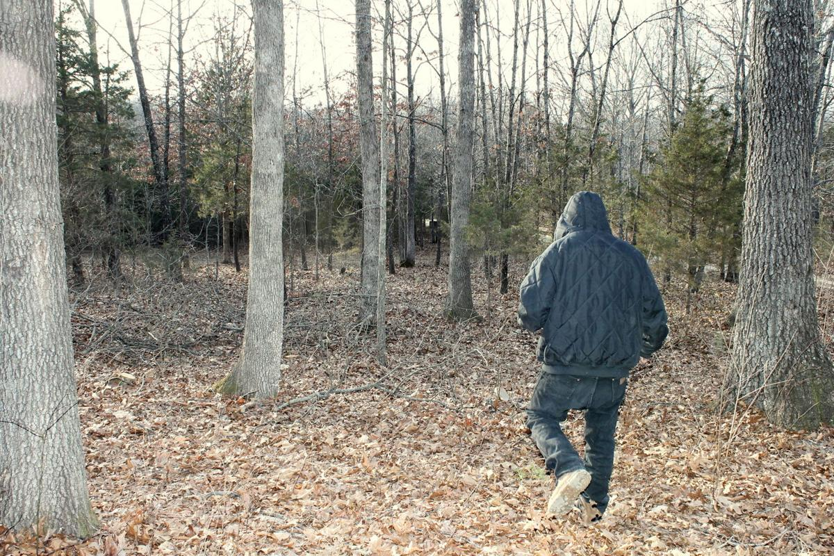 Aaron walking through the woods by his home