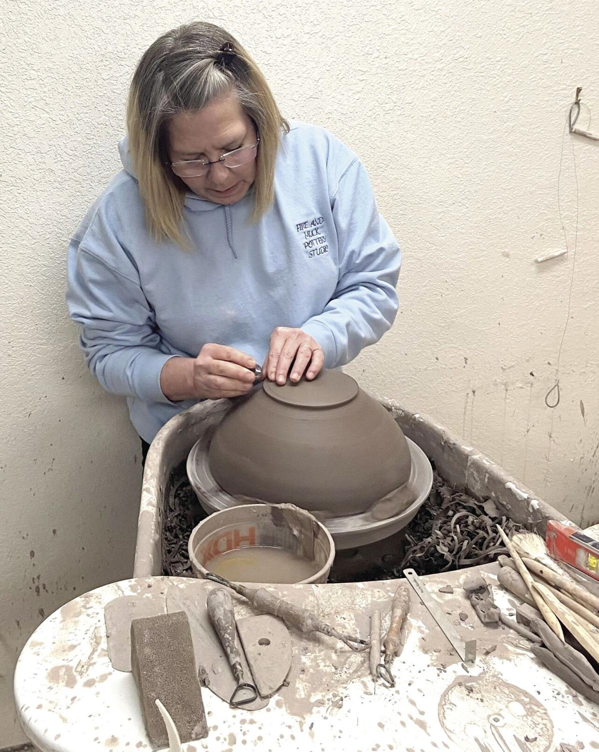 Kerry Collins trimming a bowl at her potter's wheel.