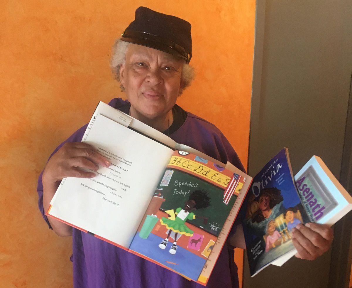 "Carolivia Herron displays her children's book ""Nappy Hair."" PHOTO BY MATT HOOKE"