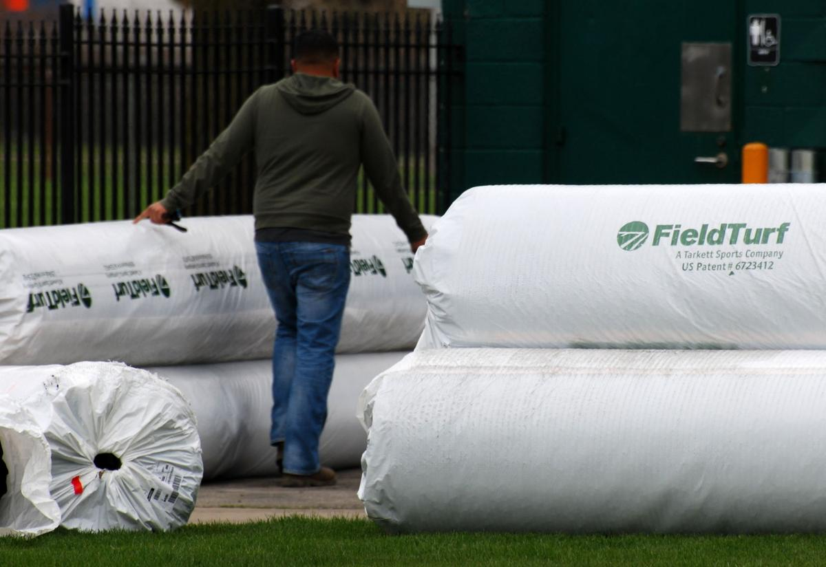 Artificial turf from FieldTurf sits on the side of the bleachers of Tom Adams Field, awaiting installation.