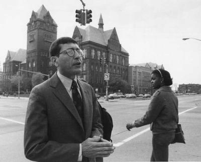 President David Adamany stands in front of WSU's Old Main on the corner of Cass Ave., and Warren, Detroit.