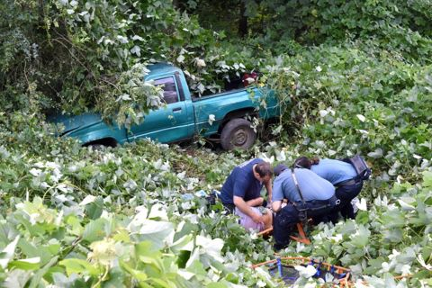 Truck rolls down embankment