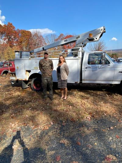 Jason Rudalavage of Highway Auto and Mia Stine, Jessup Borough manager with a donation of a bucket truck from Jessup for the Cars for Books Program.