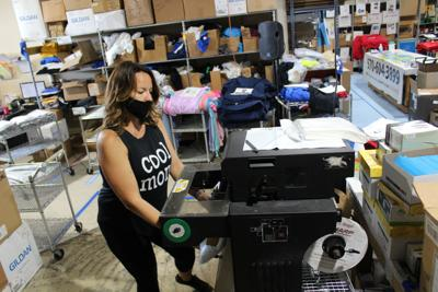 We Talk Shirty employee Angela Shotto processes a shipment of customed T-shirts for the seniors of Valley View High School.