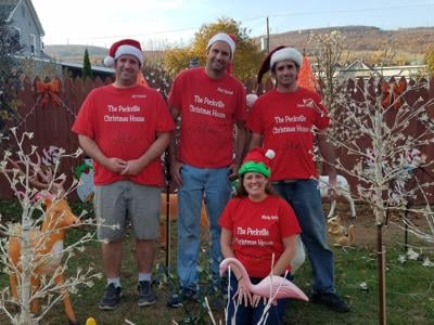 From left, Jeff, Matt, Mindy and James Harhut pose in front of some of the decorations on display at the Peckville Christmas House.