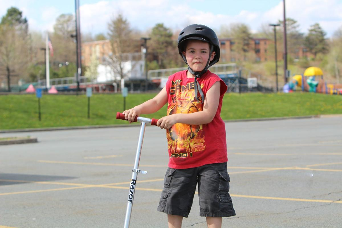 Austin Carney rides a scooter at Carbondale Area Elementary School Playground.