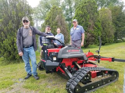 The Borough of Mayfield recently took delivery of a remote-control slope mower. The mower will be used to maintain the levees of the Mayfield Borough Flood Control Project. The mower was purchased using a Flood Mitigation Grant from the state Department of Community and Economic Development. Pictured from left are former councilman Ron Ryczak, Street Supervisor Paul Natishak, Council Vice President Diana Campbell and Mark Welliver of W.F. Welliver and Sons, supplier of the machine.