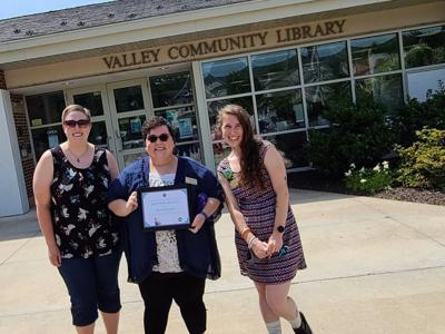 From left, Michelle Georgetti, Kristen Wallo and Fawn Contreras pose in front of Valley Community Library after Wallo received an award from Victim's Intervention Program.