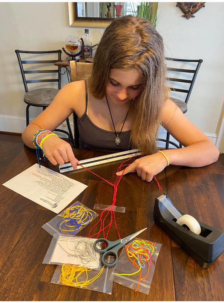 Sydney Guida works on a friendship bracelet from a kit being sold as a fundraiser by Jenny's Kloset. SUBMITTED PHOTO