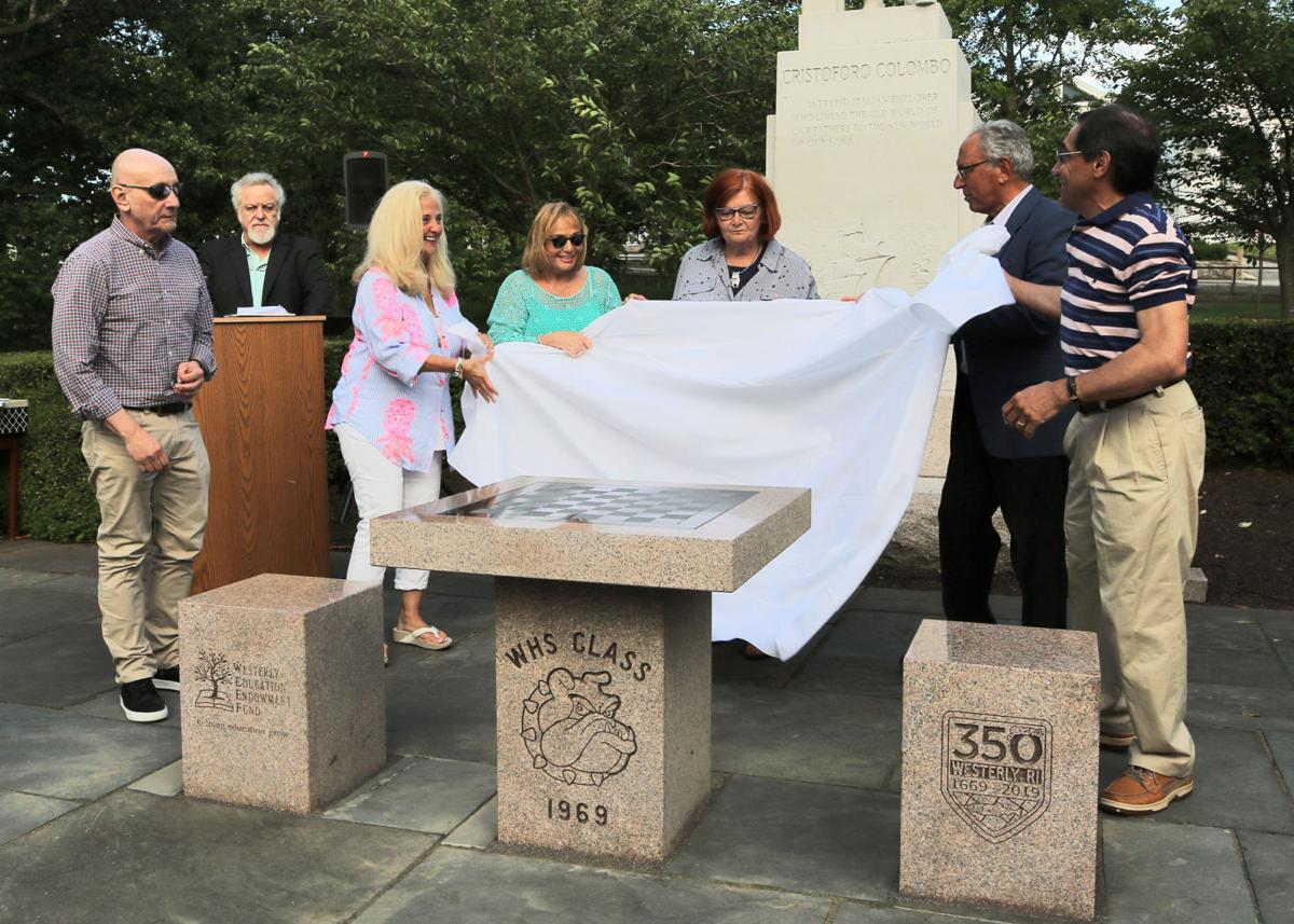 Members of the Westerly High School Class of 1969, as a celebration of Westerly's 350th Anniversary, unveil their gift to the Westerly Library and Wilcox Park Association in the form of a custom made granite chess table complete with seats and playing pieces. The dedication ceremony was held at Wilcox Park on Saturday evening, June 15th, 2019. | Jackie Turner, Special to The Sun.