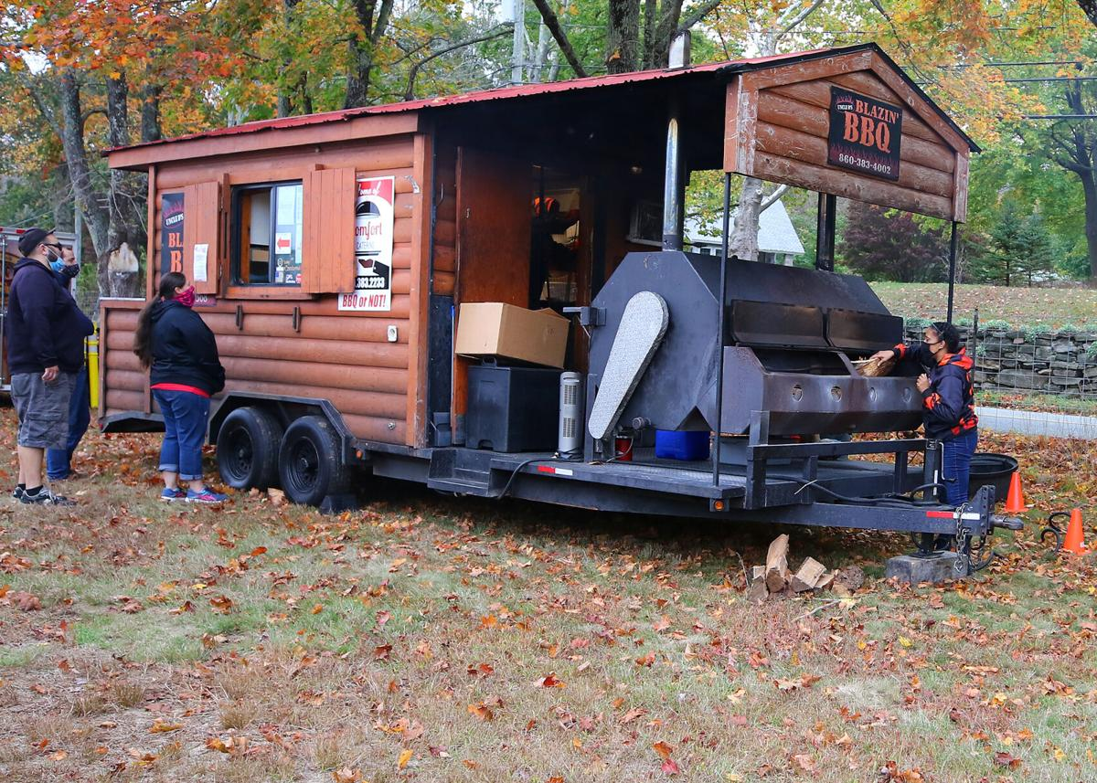 "The First Annual New England Food Truck Fest, held Saturday, October 24, 2020, brought some of Eastern Connecticut's very best truck-cooked foods and confectionaries to the North Stonington Fair Grounds. Duane and Angelina Gardner, 4th generation owners of owners of ""Uncle D's Blazin' BBQ"", were on hand with their famous rolling barbeque from Norwich, shown here being restocked with hardwood by Angelina herself. 