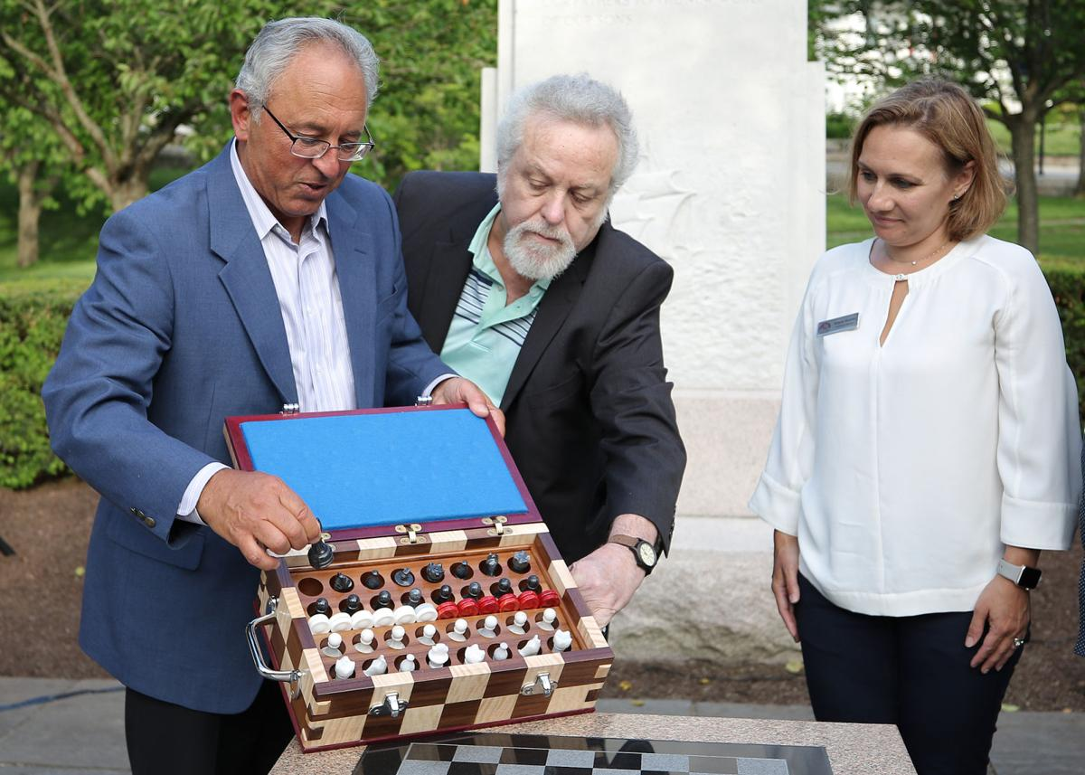 Westerly High School Class of 2019 members Joe Iacoi (left) and Roger Shea (center) unveil the custom made granite chess pieces donated as part of their granite chess board gift to the Westerly Library and Wilcox Park Association. The dedication ceremony was held at Wilcox Park on Saturday evening, June 15th, 2019. Westerly Library Executive Director Brigitte Hopkins (right) looks on | Jackie Turner, Special to The Sun.