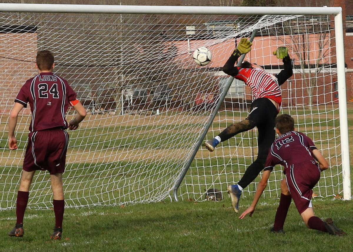Coventry goal-keeper Jonathan Rogers (25) tries to stop the shot-on-net of Wheeler's Matt Pierce (12) in the Wheeler vs Coventry boys' varsity CIAC Class-S State Soccer playoffs on Monday afternoon, November 11, 2019, at Wheeler High School in North Stonington, CT. Roger's score was a result of his head deflection towards the net. Pierce's teammate Scott Pion (24) looks on. | Jackie L. Turner, Special to The Sun.
