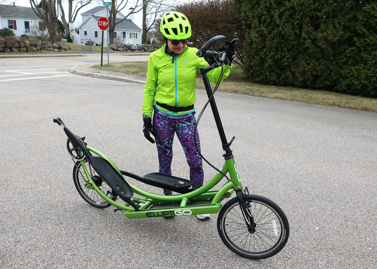 """Westerly resident Mary Ann Janiszewski looks over her """"ElliptiGo"""" bicycle during an exercise break at Misquamicut Beach on Saturday afternoon, March 21, 2020. Marry Ann claims the bike's unique stand-up design provides her a better work-out while minimizing the shock to her knees. 