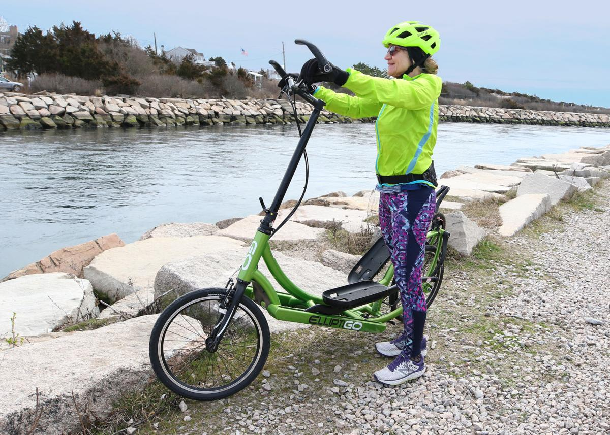 """Westerly resident Mary Ann Janiszewski looks over the Weekapaug Breachway during an exercise break at Misquamicut Beach on Saturday afternoon, March 21, 2020. Her """"ElliptiGo"""" stand-up bicycle, shown here on the west side of the breachway, is unique to the industry as it has no seat and utilizes an elliptical pedaling motion instead of the standard circular motion found on other bikes. 