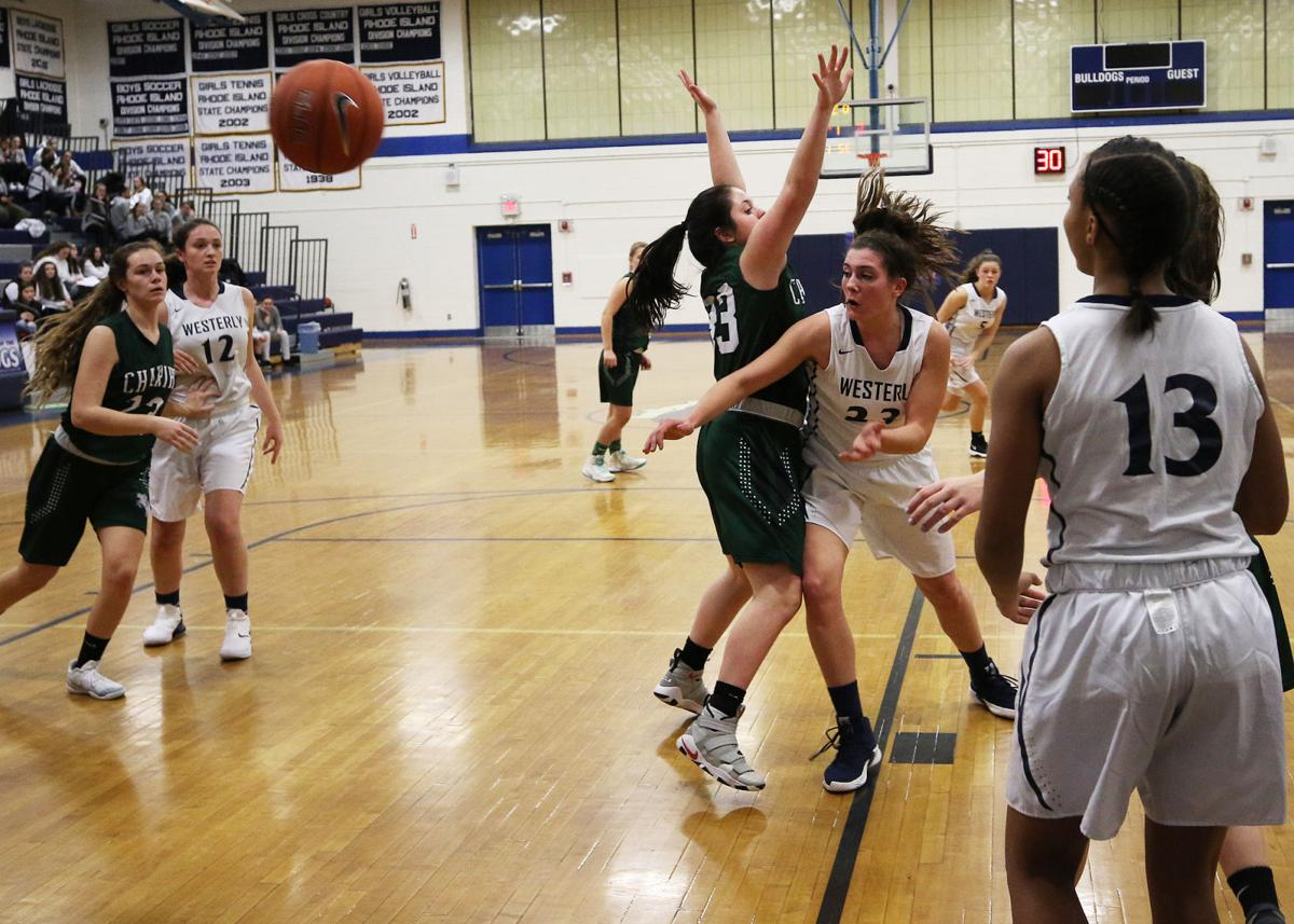 Westerly's Megan Albamonti (23) tries to reach a pass while Chariho's Shleby Roode (33) defends. The Westerly Bulldogs girls varsity basketball team took on the Chariho Chargers in the 35th Annual WCCU Holiday Basketball Tournament playoffs on Thursday evening, December 27th, 2018 at Westerly High School. | Jackie L. Turner, Special to The Sun.
