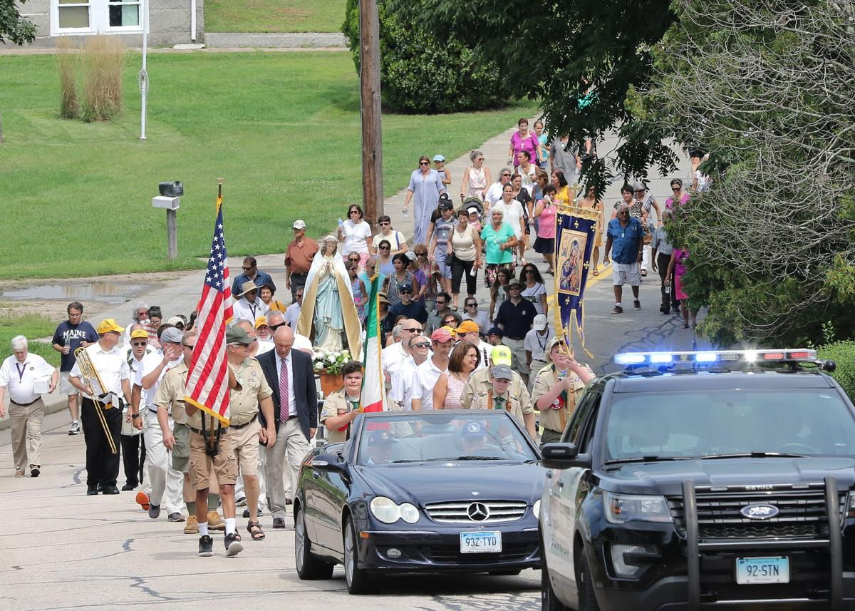 Down a hill and up a hill, the St Michaels Feast of Maria Assunta procession winds its way along Pawcatuck's Robinson Street on Sunday, August 18th, 2019. The procession, now in its 99th year, follows a pre-determined route before ending in the St Michael school's parking lot where a buffet-style Italian meal is provided.   Jackie Turner, Special to The Sun.