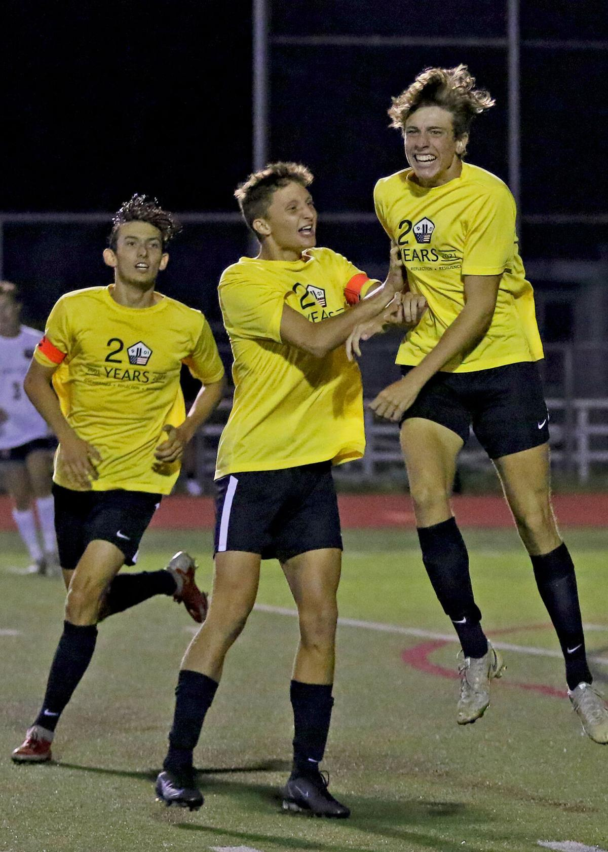 Stonington's Ryan Turner (right) celebrates after making the first goal of the evening in the 2021 Piver Cup Boys Soccer Tournament final played Saturday evening, September 18, 2021, at Stonington High School in Pawcatuck. Celebrating with him are Bear's teammates William deCastro (left) and Wynn Hammond (center). Stonington would eventually go on to win 2-0 over Fitch.   Jackie L. Turner, Special to The Sun.