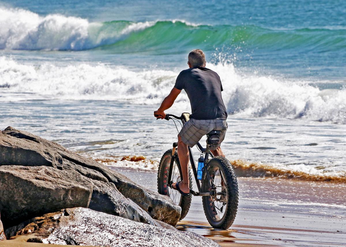 092019 WES Cyclist rides along beach 1225.JPG